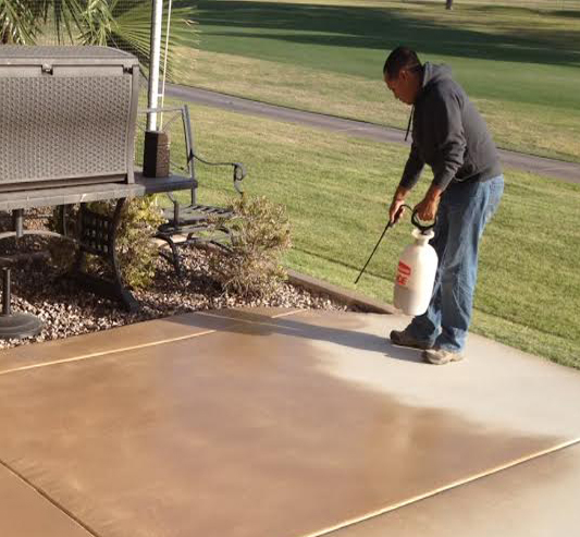 Spraying stain on concrete with gallon sprayer.